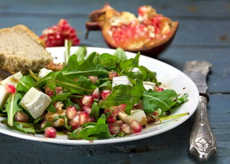 rocket salad with  feta cheese and pomegranate on an rustic wood