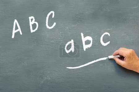 Hand writing on a chalkboard the letters abc