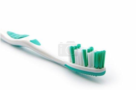 Photo pour Brosse à dents verte sur fond blanc, gros plan avec une faible profondeur de champ - image libre de droit