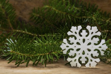 white snowflake star and fir branches on rustic wood as a Christ