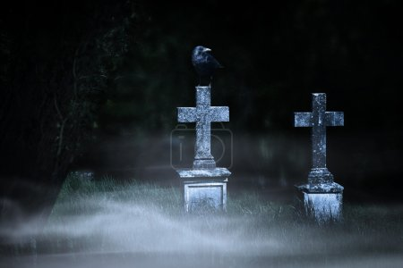 halloween concept, stone crosses at night on the foggy cemetery
