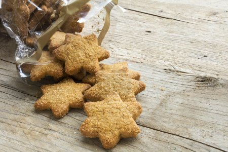 Photo for Christmas cookies in star shape falling from a cellophane bag on a rustic wooden table, copy space - Royalty Free Image