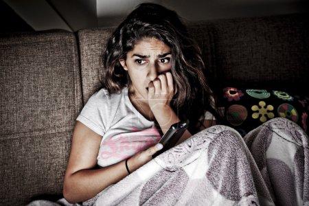 Photo pour Peur jeune femme regardant la télévision. jeune fille brune assise sur le canapé avec la télécommande - image libre de droit