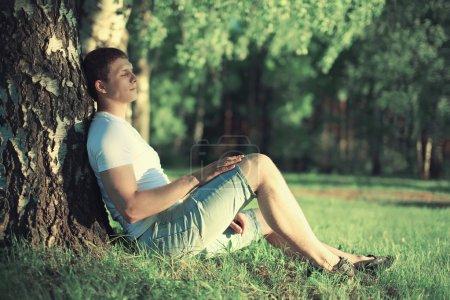 Photo pour Homme pensif assis près d'un arbre avec les yeux fermés méditant et profitant du chaud coucher de soleil d'été - image libre de droit