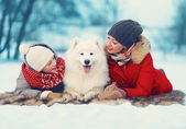 Beautiful happy family, mother and son walking with white Samoye