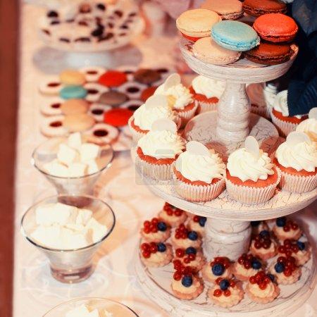 Photo pour Sweet table de buffet coloré avec des macarons et gâteaux - image libre de droit
