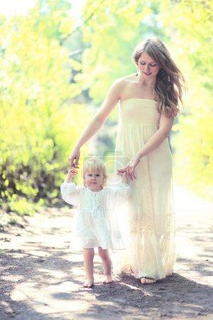 Photo pour Photo ensoleillée mère et enfant marchant pieds nus dans la forêt, maman aide le bébé à faire les premiers pas un jour d'été - image libre de droit