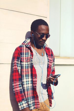 Fashion portrait of stylish young african man listens to music o
