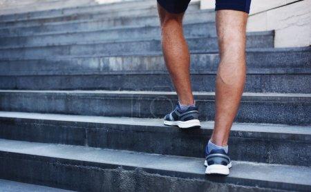 Photo pour Sport, fitness et mode de vie sain concept - homme courant dans la ville, pieds de coureur masculin sur les marches des escaliers gros plan sur fond urbain - image libre de droit