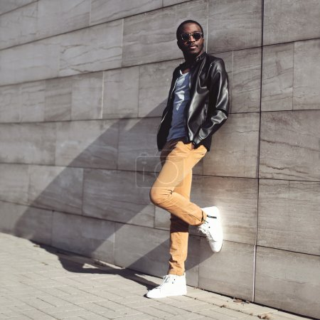 Street fashion, stylish young african man wearing a sunglasses a