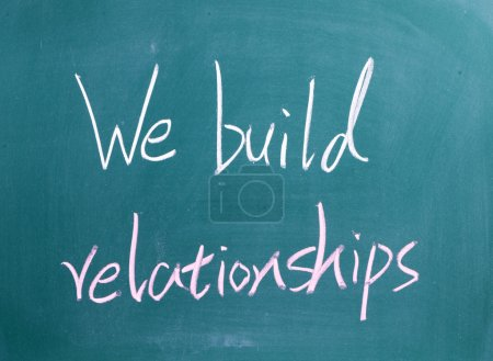 Photo for We build relationships sign on blackboard - Royalty Free Image