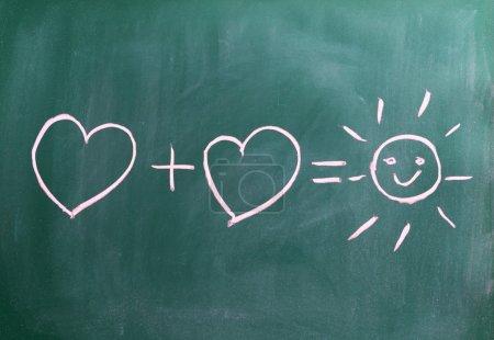Photo pour Successful relationship two hearts and a sun on chalkboar - image libre de droit