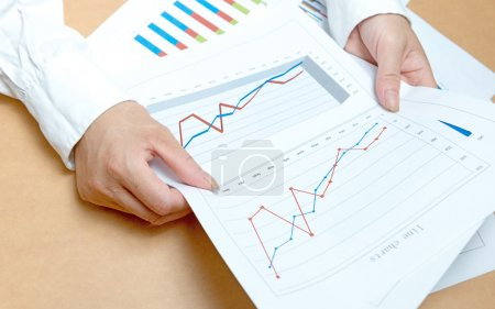 Woman hands with charts and papers