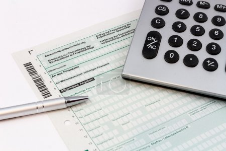 Form of income tax return with ball pen and pocket calculator