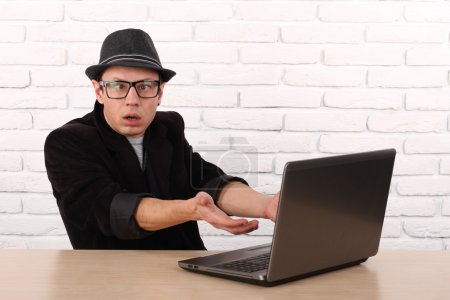 Photo pour Choqué jeune homme d'affaires à l'aide d'un ordinateur portable en regardant l'écran d'ordinateur soufflé dans la stupeur assis à l'extérieur du bureau de l'entreprise. Expression du visage humain, émotion, sentiment, perception, langage corporel, réaction - image libre de droit