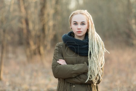Young beautiful blonde hipster woman in scarf and parka with dreadlocks hairstyle posing on a blurry forest background