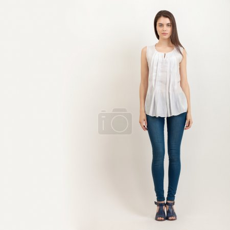 Full length portrait of young calm beautiful brunette woman posing for model tests against white background