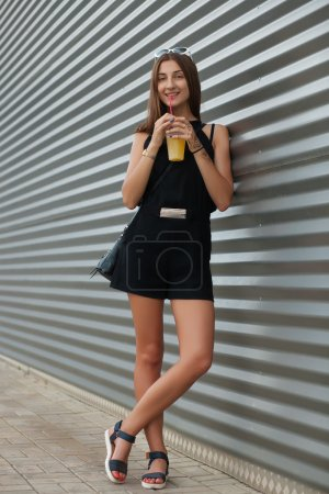 Full length portrait of stylish young beautiful hipster woman in little black dress drinking lemonade outdoors