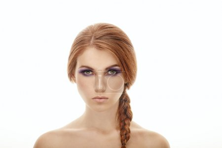 Closeup beauty portrait of a young beautiful woman with violet eyes makeup and braided hairstyle on isolated background