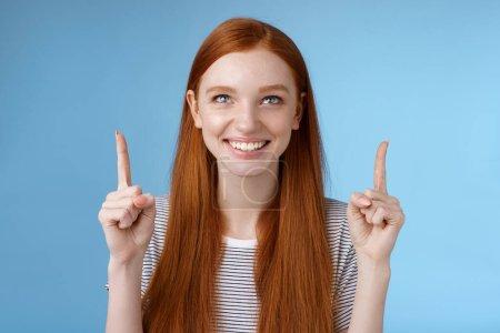 Amüsiert aufgeregt glücklich lächelnd rothaarige Mädchen Blick zeigt nach oben grinsend freudig beobachten genial Open-Air-Performance stehend freudig zeigt coole Sache anzeigt Produkt, blauer Hintergrund