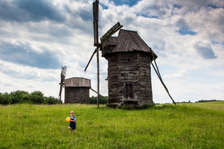 Windmills and children in the field under the clouds.