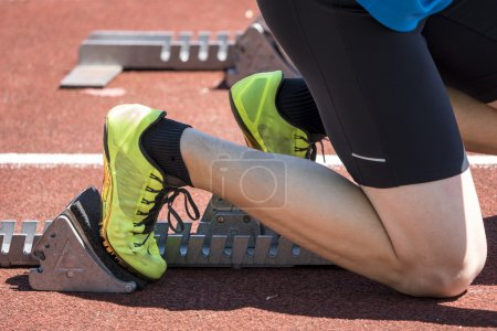Photo for Man in sprint start in track and field - Royalty Free Image