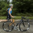 Triathlete with a bicycle on the road...