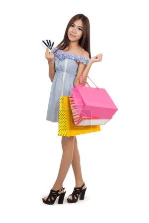 Photo pour Belle femme asiatique à pied avec les sacs à provisions montrent les cartes de crédit isolés sur fond blanc - image libre de droit
