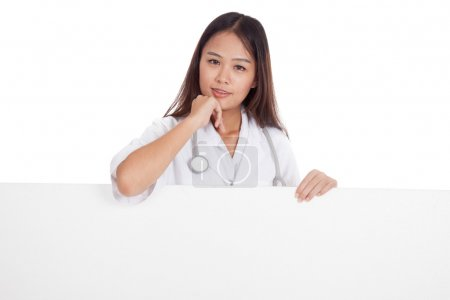 Young Asian female doctor standing behind blank white billboard