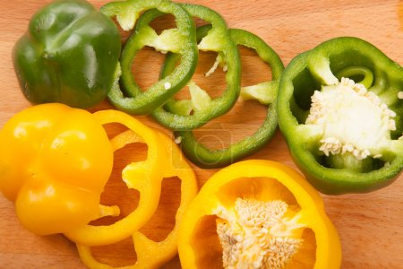 Cut yellow and green bell peppers on cutting board