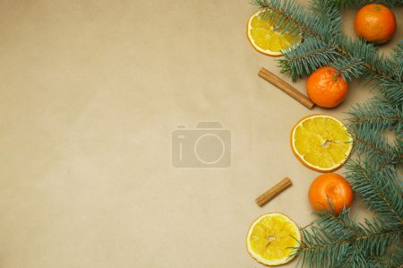 Fir tree branche with mandarine orange and dried orange slices on craft paper