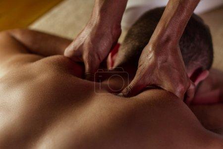 Photo pour Homme a deep tissue massage sur le dos. - image libre de droit