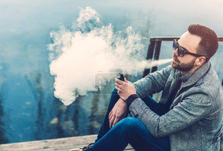 Man with beard  vaping outdoor