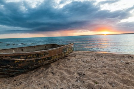 Rusty row boat on the sand at sunset