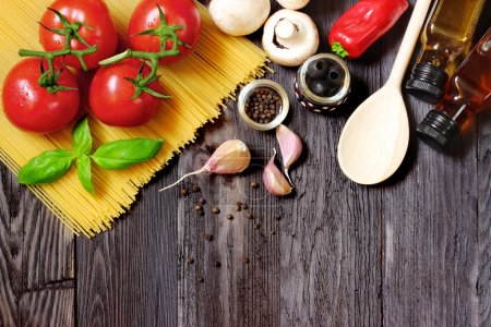 Fresh vegetables and pasta on dark wood