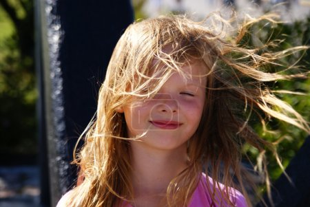The wind blows the hair of blond girl