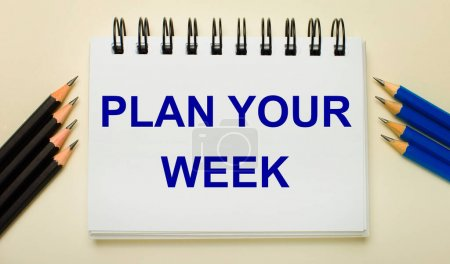 Photo for On a light background, a white notebook with the text PLAN YOUR WEEK and black and blue pencils on the sides. - Royalty Free Image