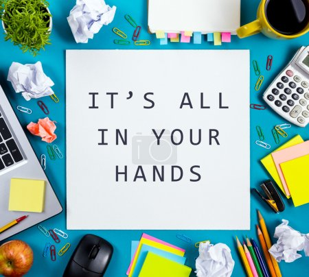Its all in your hands. Office table desk with supplies, white blank note pad, cup, pen, pc, crumpled paper, flower on blue background. Top view