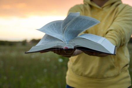 Female hands holding opened hardback book, diary against sunset