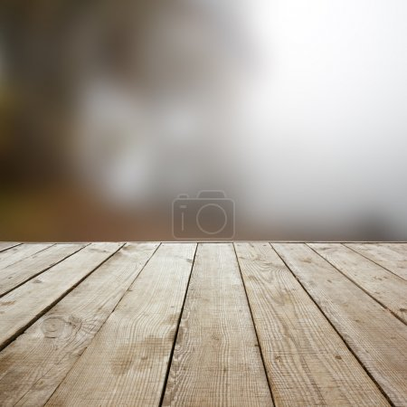 Wooden perspective floor with planks on blurred natural autumn background, can use for display or montage your products template. Copy space. Vintage toned.