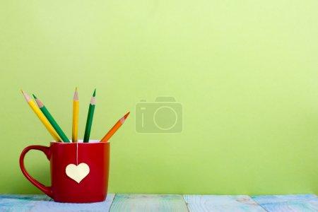 Photo pour Composition avec vieux livres cartonnés vintage et tasse rouge en forme de cœur jaune et crayons sur fond vert et table de terrasse en bois. Livres d'empilage. Retour à l'école. Copiez l'espace. Contexte de l'éducation. - image libre de droit