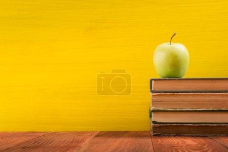 Photo pour Empilement de livres rigides colorés sur fond jaune. Composition avec de vieux livres à dos rigide vintage, un journal, des pages ventilées sur une table de terrasse en bois. Des livres empilés. Je retourne à l'école. Espace de copie. Formation initiale . - image libre de droit