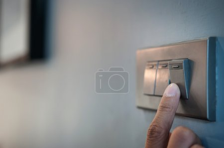 Finger is turning on a light switch.