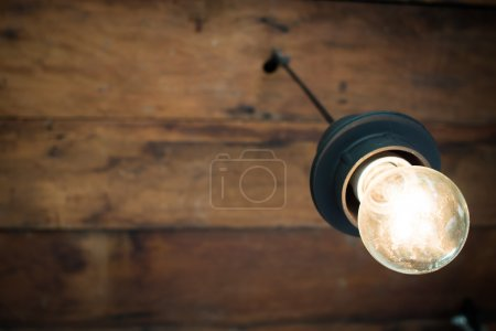 decorative antique light bulb with old wooden ceiling background