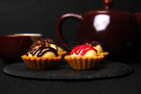 Photo pour Accent sélectif chocolat maison or et fraise garniture tarte au fromage avec tasse à thé et théière aperçu sur fond sombre. - image libre de droit