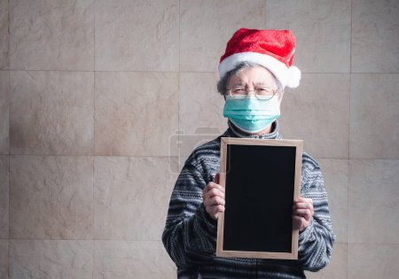 Photo for Portrait of an elderly Asian woman wearing a Santa Claus hat, mask, holding a small blackboard, and looking at the camera while standing with a vintage background. Concept of aged people and festival. - Royalty Free Image