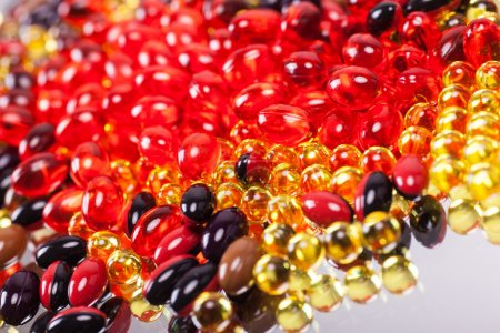 Photo for A scattering of colored capsules and tablets, close-up, photograph with depth of field - Royalty Free Image
