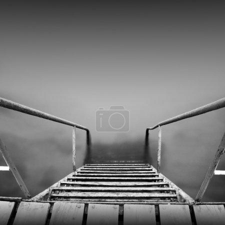 Foto de Pasos a ninguna parte. hermosa minimalista blanco y negro paisaje marino con escaleras en el agua de mar y la leche. tomada durante el día con larga exposición - Imagen libre de derechos