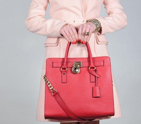 Red stylish glamorous female leather bag on pure background