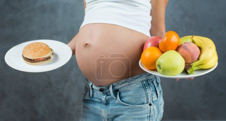 Close up of a cute pregnant belly tummy and healthy food. Pregna